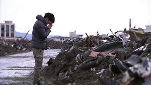 震災後の復興を誓い、犠牲者に祈りを捧げる人